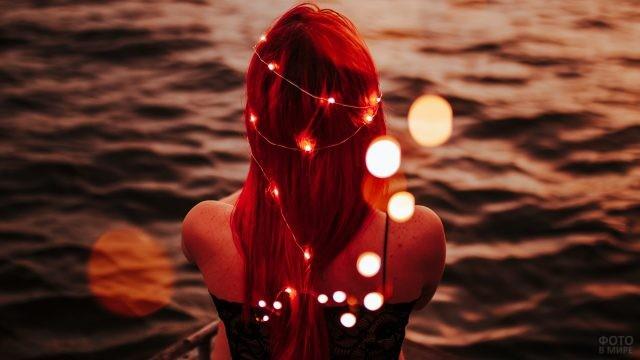 Рыжеволосая девушка с гирляндами на теле