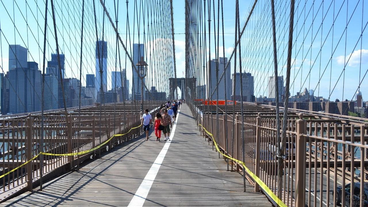 Люди гуляют по подвесному мосту