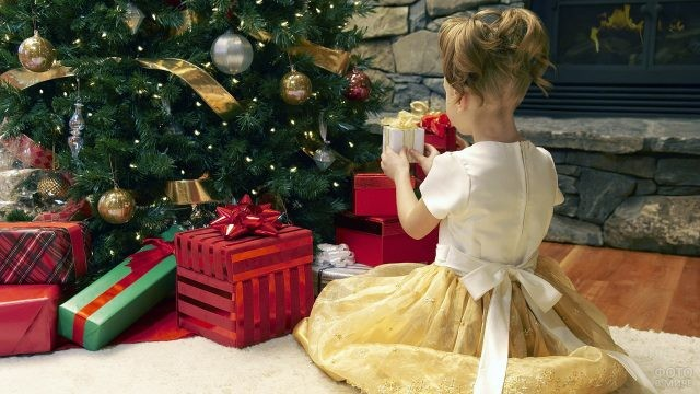 Девочка в нарядном платье разглядывает пока запакованные подарки под ёлкой