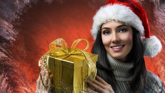Девушка в новогодней шапочке держит в руках золотую подарочную коробку