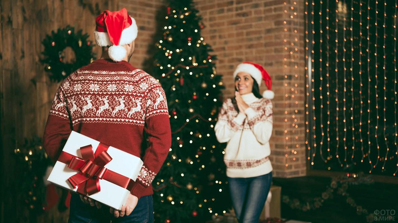 Девушка в предвкушении новогоднего подарка в руках молодого человека за спиной