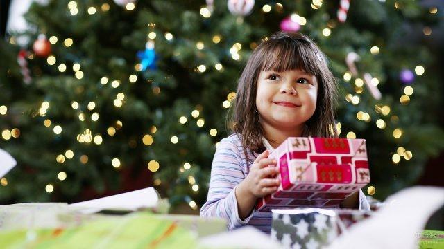Довольная малышка с новогодним подарком на фоне нарядной ёлки