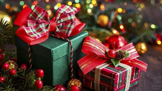 Две красно-зелёных подарочных коробки в одном стиле среди новогодних украшений