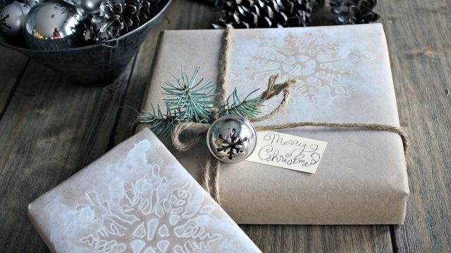Еловая веточка, трафаретный рисунок снежинки и бубенчик на новогодних подарках в эко-стиле