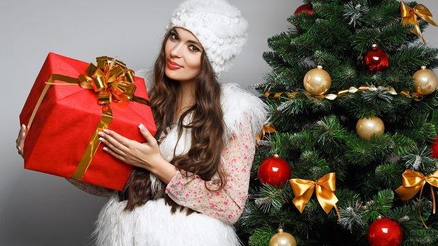Красивая девушка с большим новогодним подарком рядом с ёлкой
