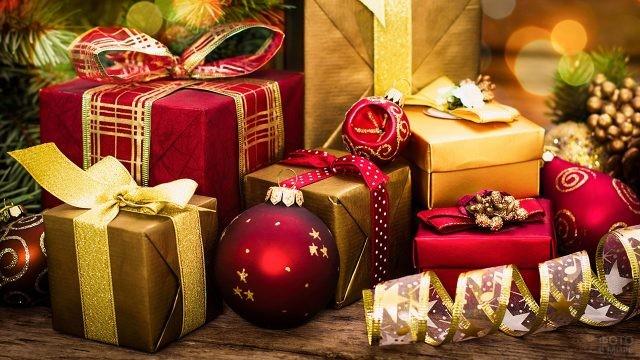 Красиво оформленные красно-золотые новогодние подарки среди ёлочных шаров