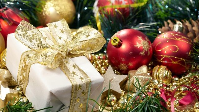 Красиво оформленный новогодний подарок среди ёлочных игрушек