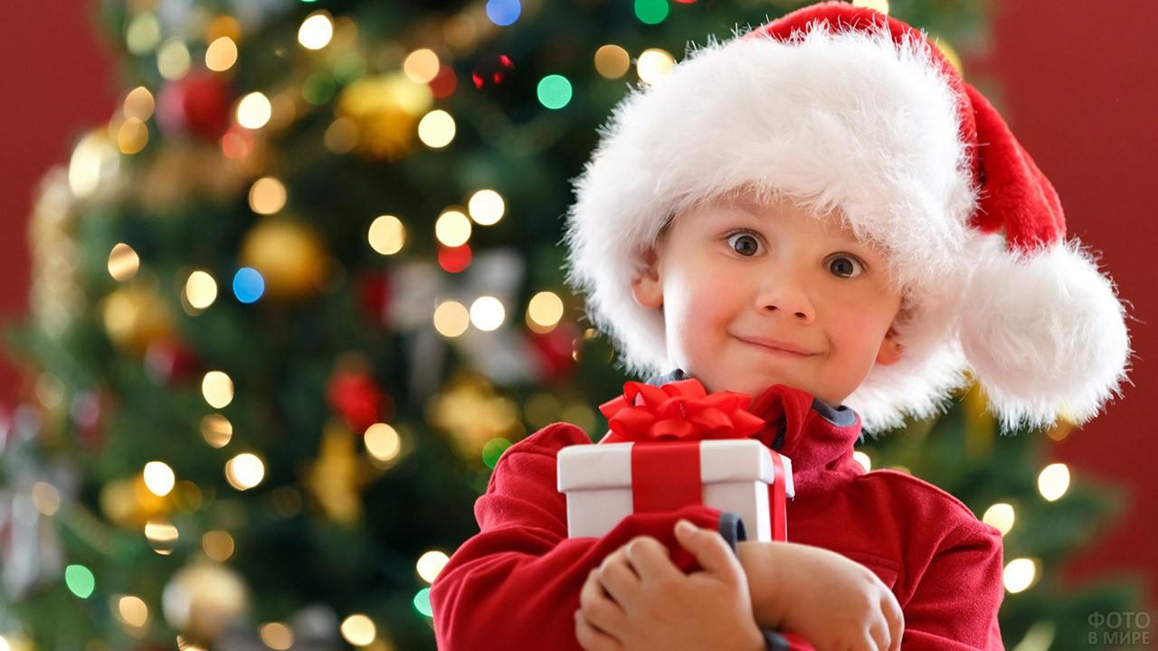 Малыш в новогодней шапке в обнимку с подарком у нарядной ёлки