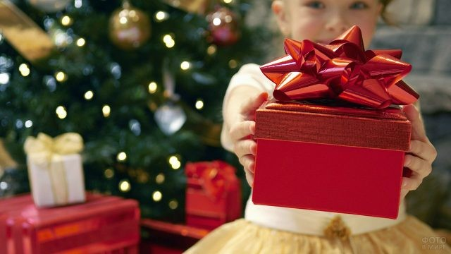 Малышка в нарядном платье протягивает вперёд красную подарочную коробку