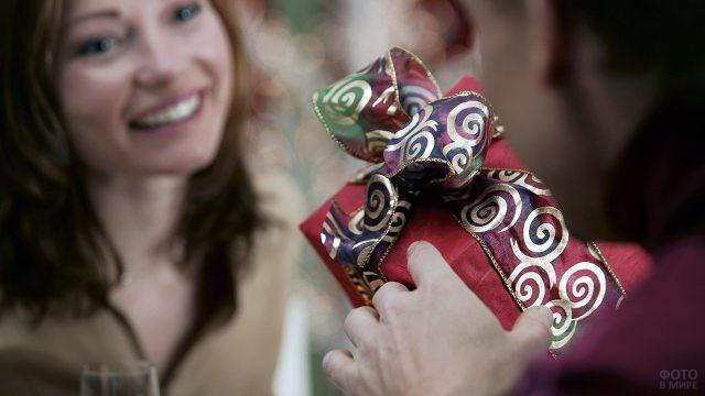 Мужчина дарит любимой новогодний подарок в красно-золотой упаковке