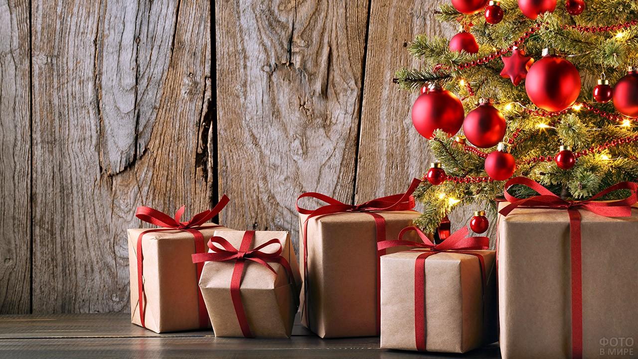 Новогодние подарки в эко-стиле с красными ленточками под ёлочкой с красными шариками