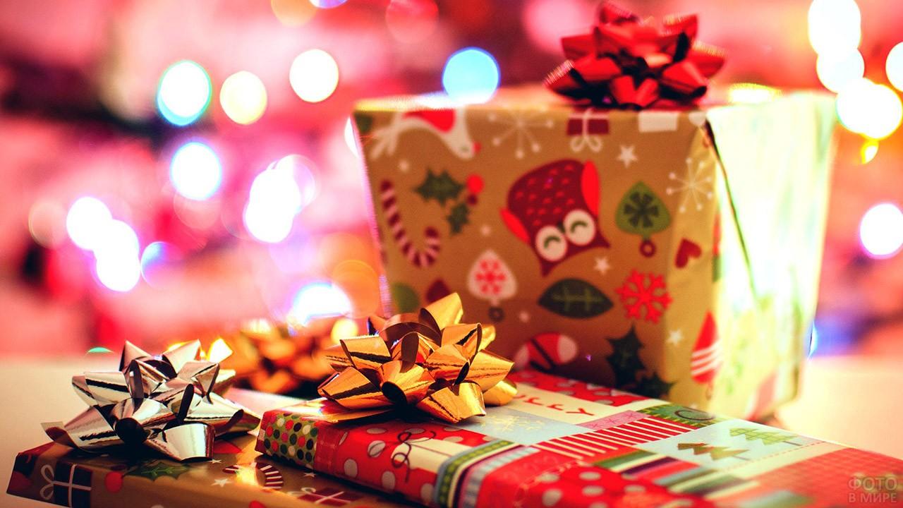 Новогодние подарки в пёстрой упаковочной бумаге на фоне огоньков