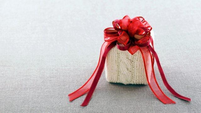 Новогодний подарок в милой вязаной упаковке с красным бантом