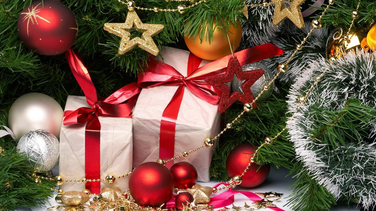 Подарки с красными ленточками под нарядной новогодней ёлкой