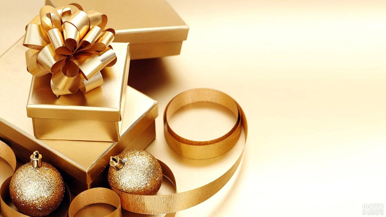 Подарки в золотистых коробочках среди золотистых ёлочных игрушек