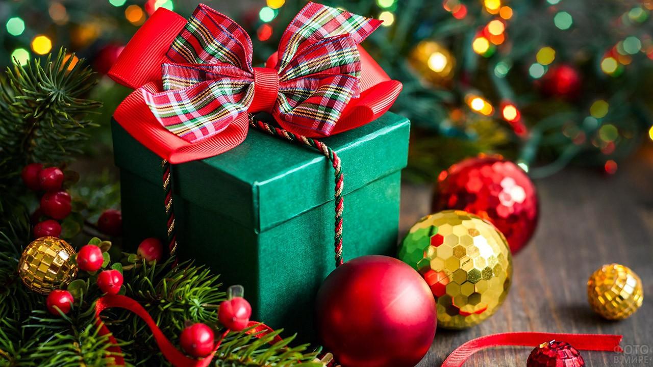 Подарок в новогодней красно-зелёной гамме среди ёлочных украшений