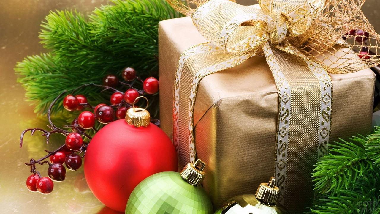 Подарок в золотой обёртке среди еловых веток и шариков