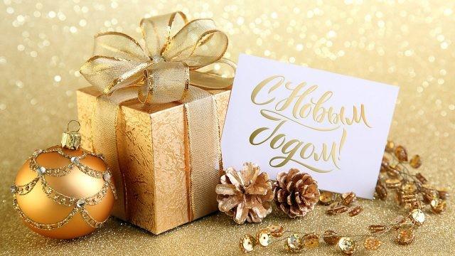 Поздравительная карточка рядом с подарочной коробочкой, ёлочными шариками и шишками в золотой гамме