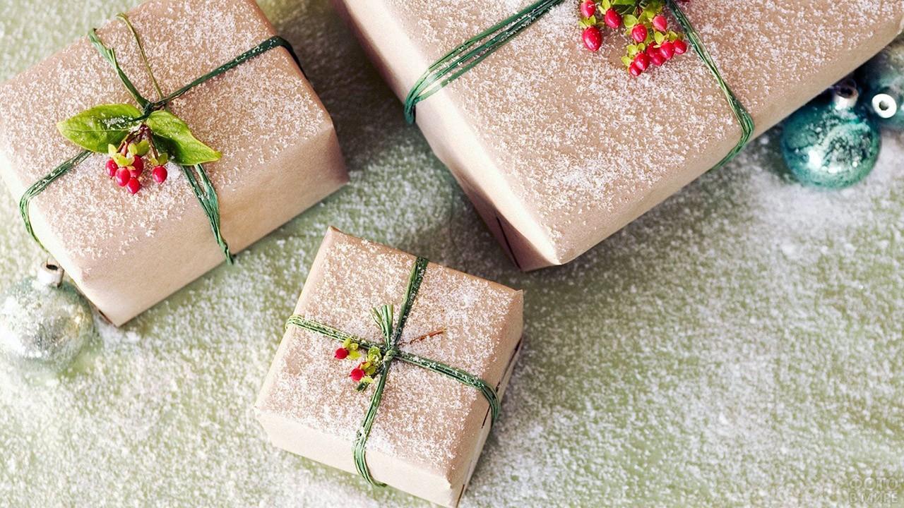 Присыпанные снегом новогодние подарки в крафт-бумаге