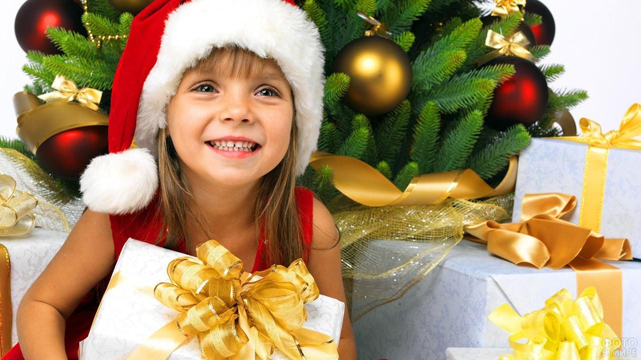 Счастливая маленькая девочка с большим подарком под новогодней ёлкой