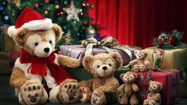 Семья плюшевых мишек среди подарков под новогодней ёлкой