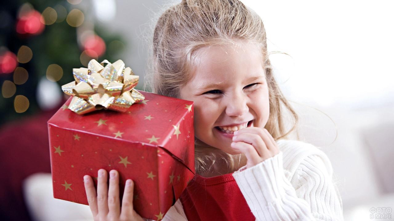 Смущённая девочка с новогодним подарком в красной коробке