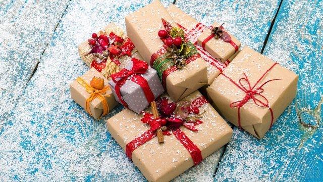 Стильно оформленные подарки на заснеженном деревянном крыльце
