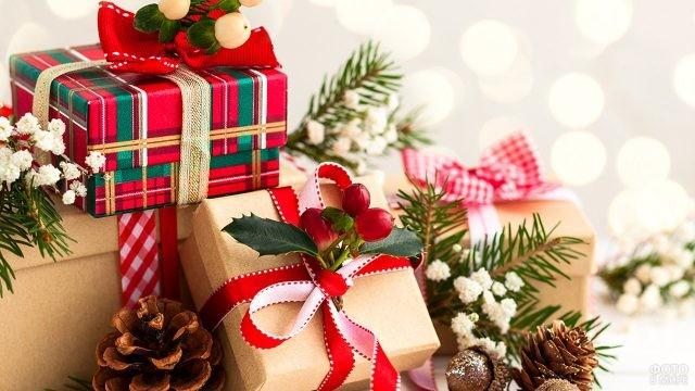 Стильно оформленные подарочные коробки среди еловых шишек и веток с цветами