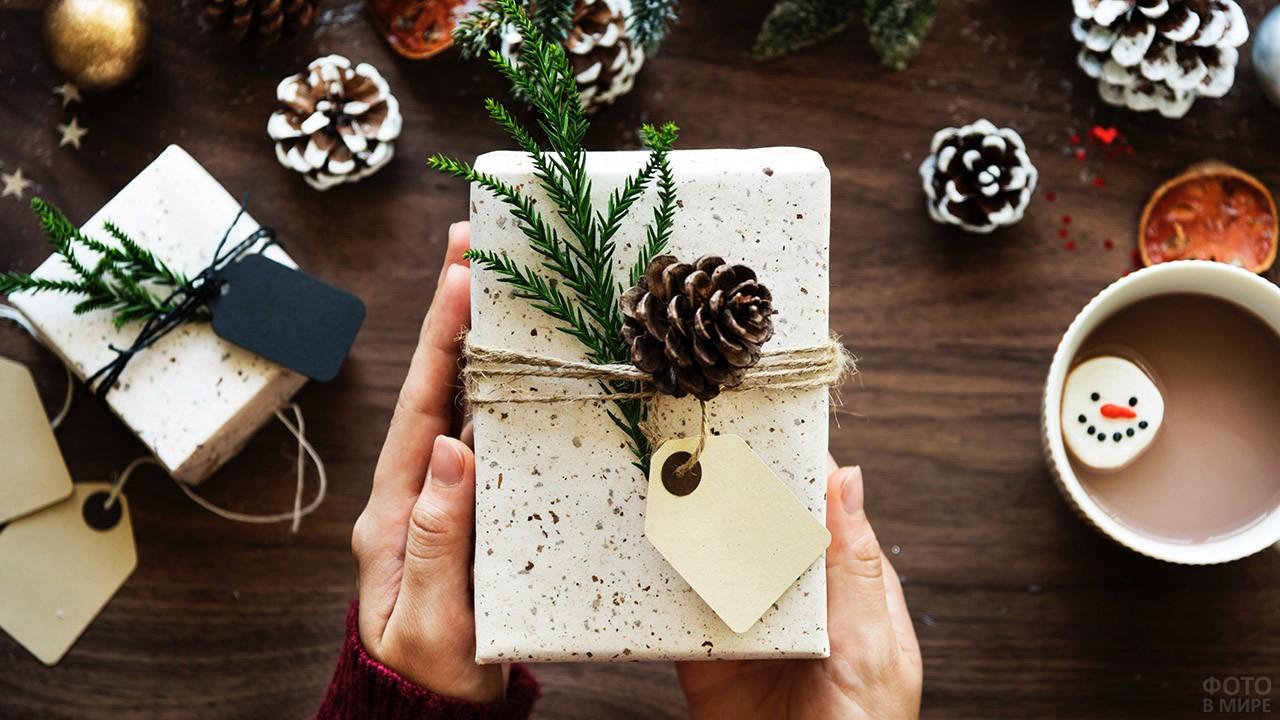 Стильно оформленный новогодний подарок в руках над столом