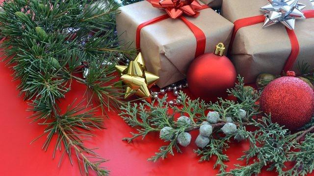 Стильные подарки в крафтовой бумаге с яркими бантиками среди новогодних украшений