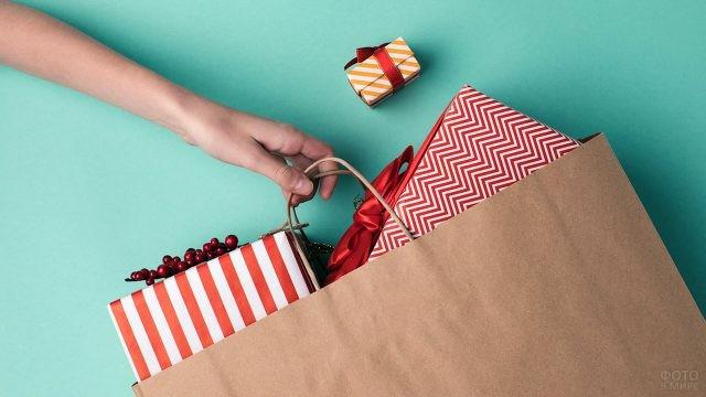 Выглядывающие из крафт-пакета новогодние подарки в красно-белых упаковках