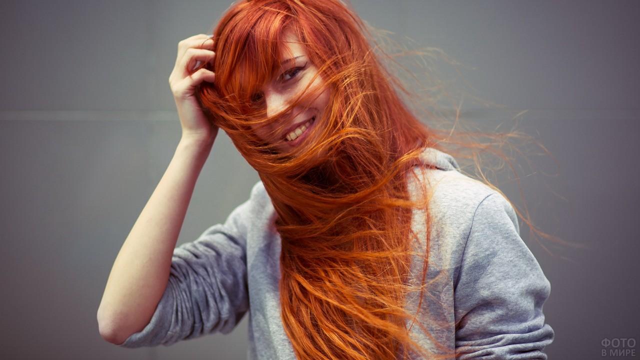Девушка в толстовке поправляет волосы