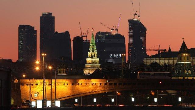 Светящие кремлёвские башни на фоне силуэта Москва-Сити