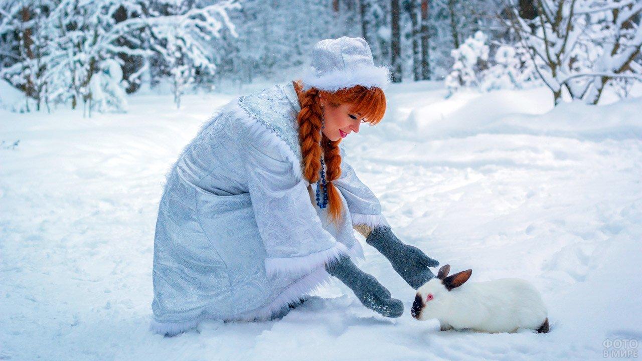 Снегурочка с рыжими косичками протягивает руки к кролику в зимнем лесу
