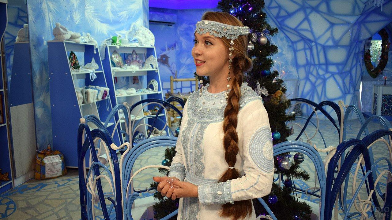 Снегурочка у ёлки в сказочном голубом интерьере