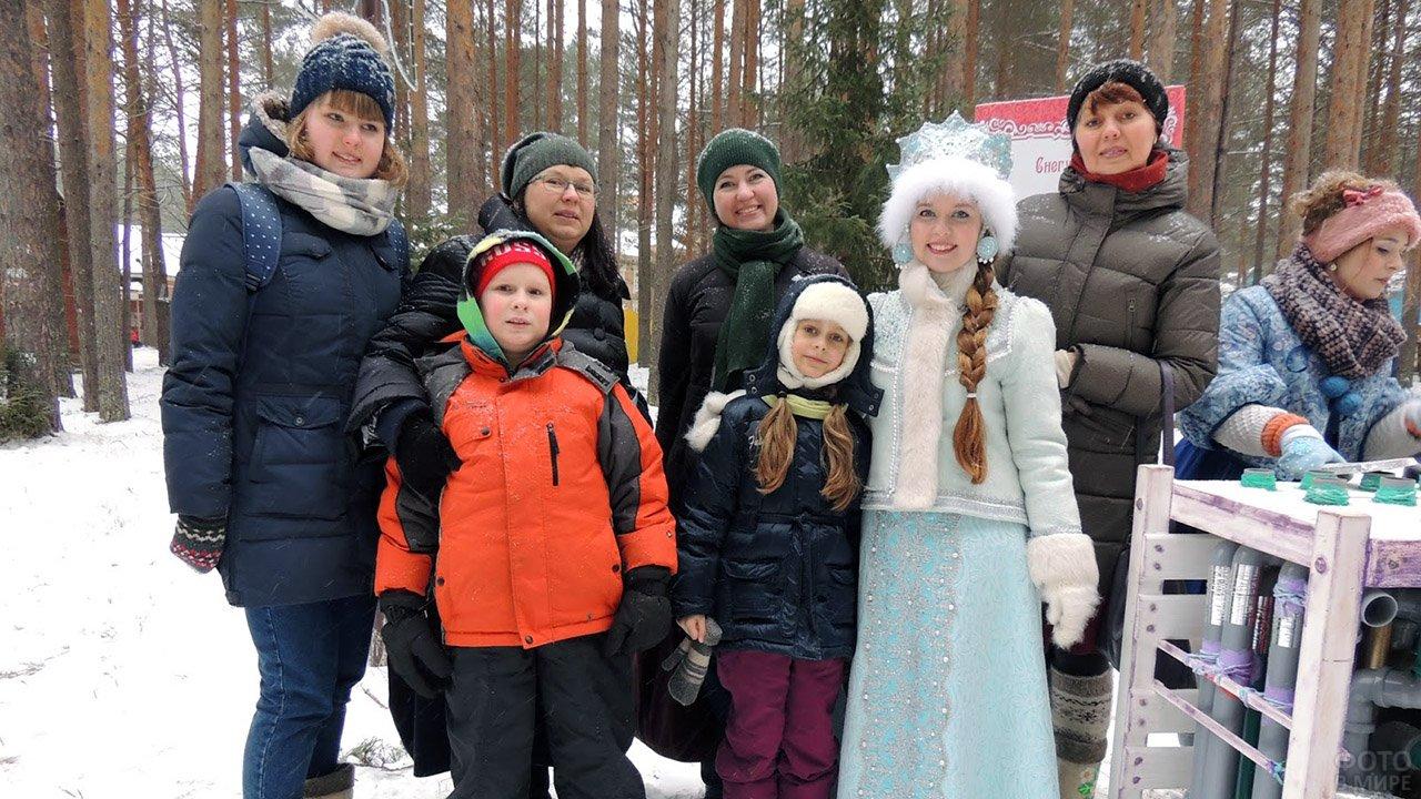 Снегурочка в окружении детей и их мам в городском предновогоднем парке