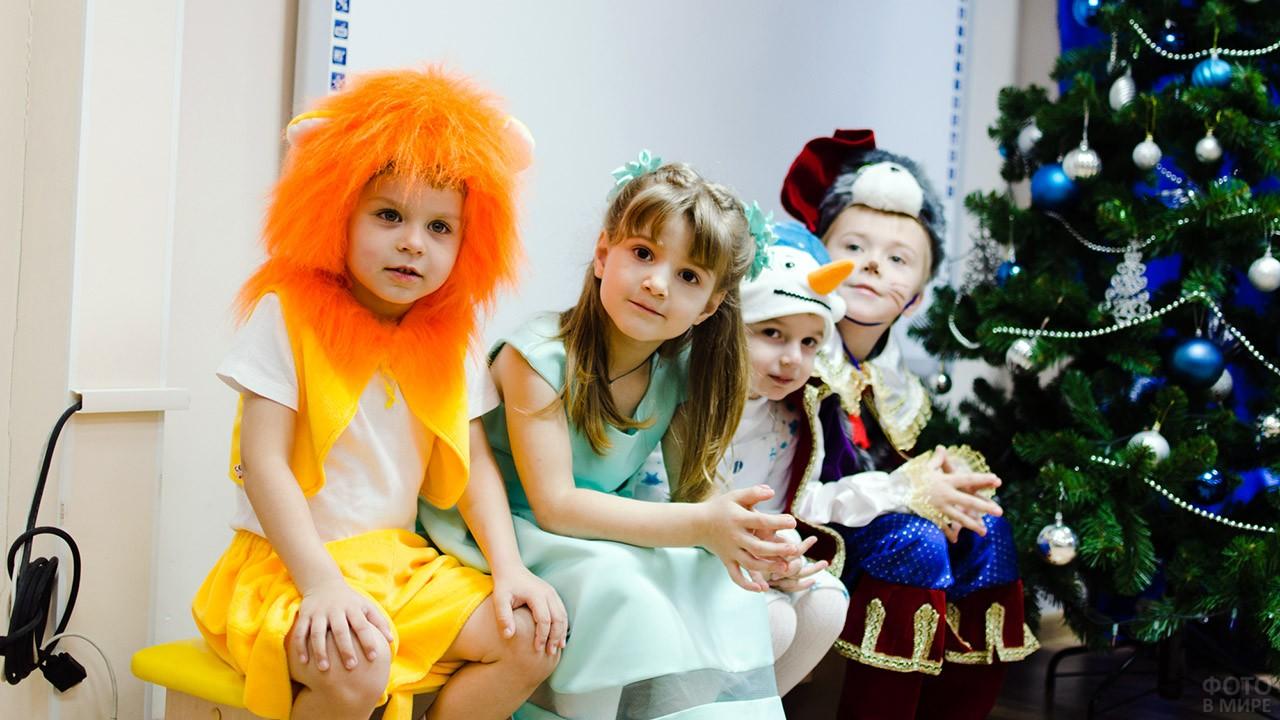 Дети в маскарадных костюмах у новогодней ёлки