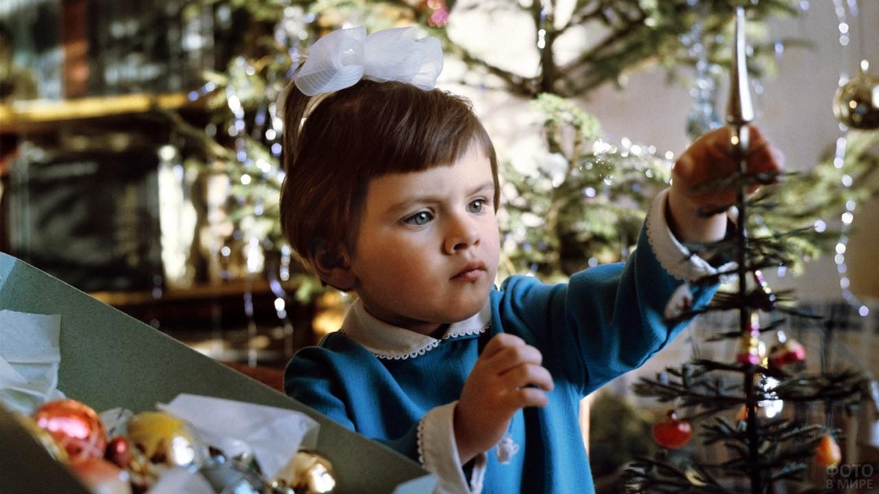Девочка украшает новогоднюю ёлочку