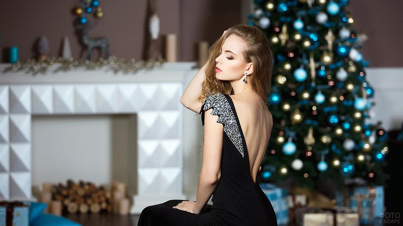 Красивая девушка в вечернем платье перед ёлкой