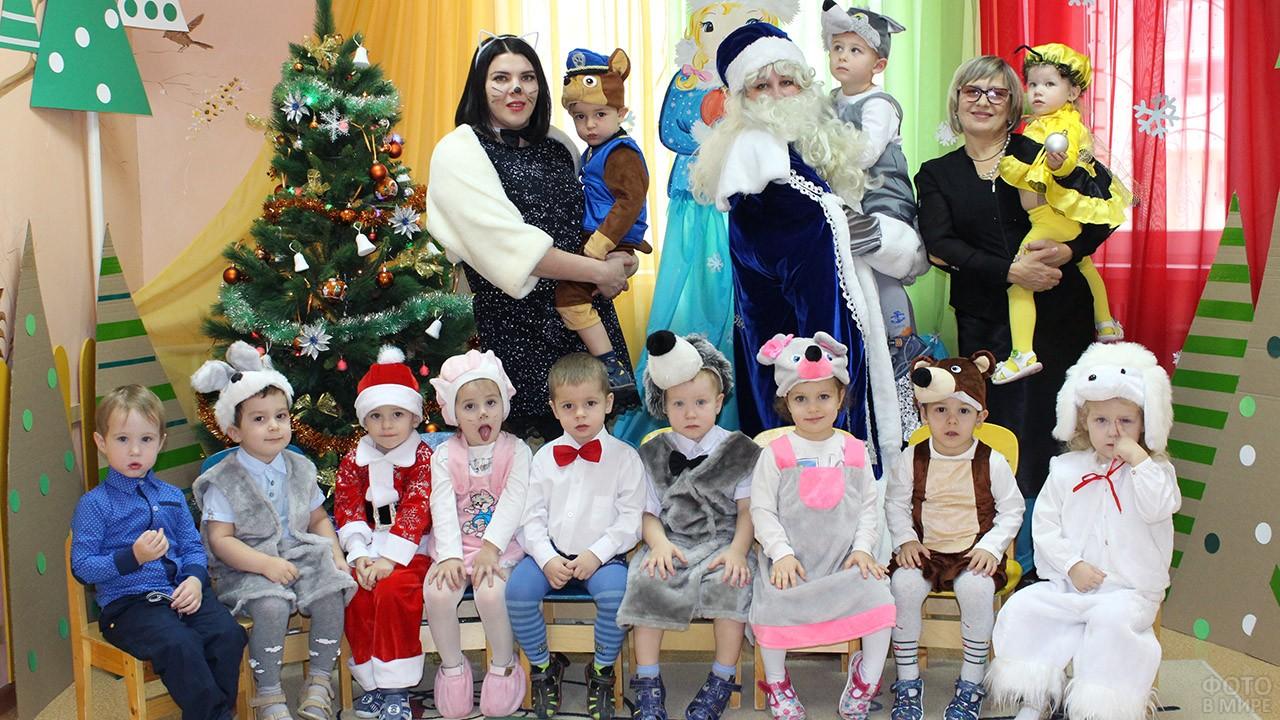 Малыши в новогодних костюмах у ёлки в детском саду