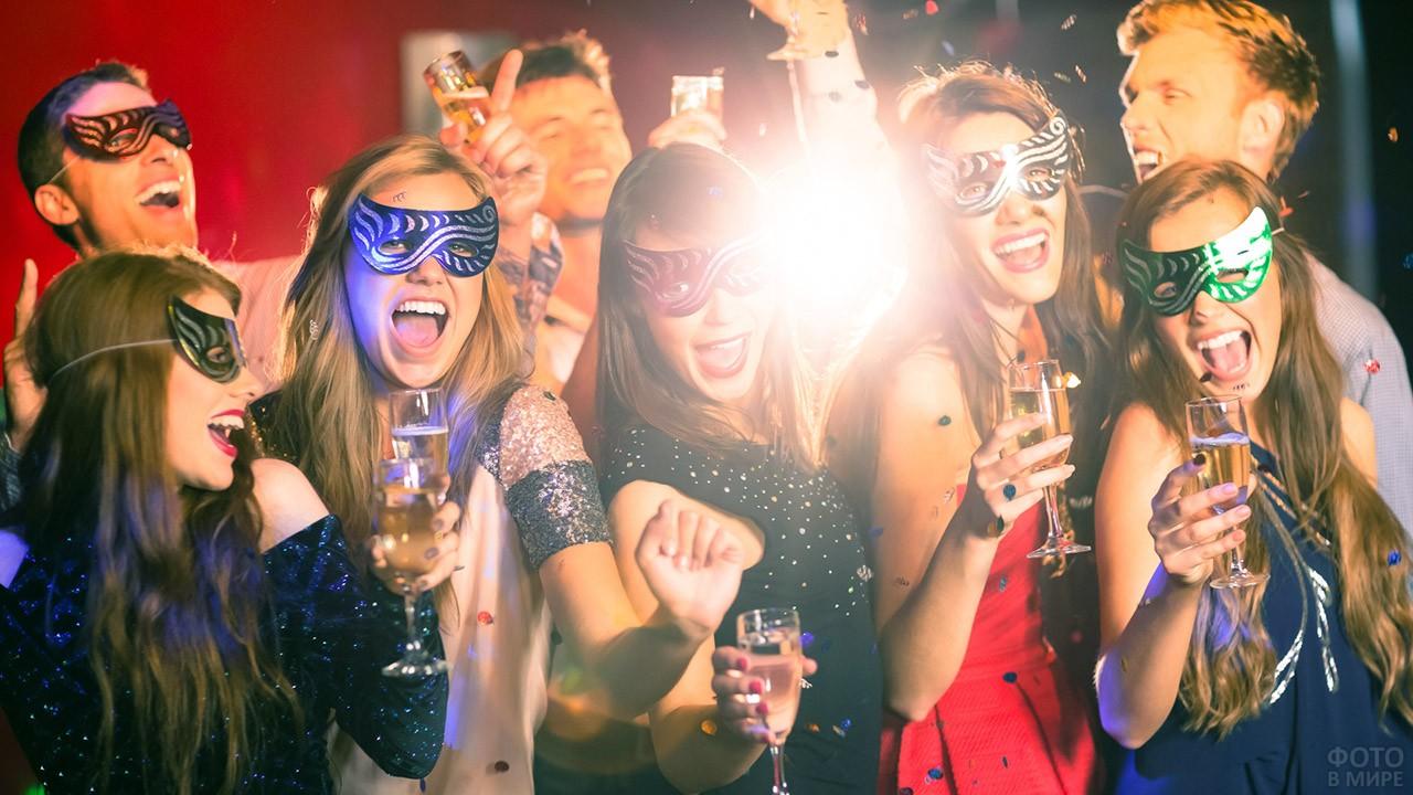 Молодёжь в маскарадных масках с бокалами шампанского