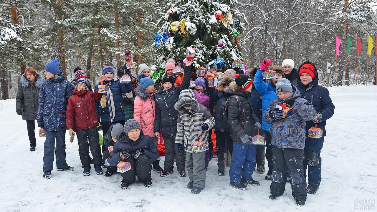 Школьники с подарками у заснеженной ёлки в парке