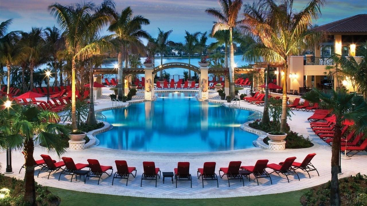 Пляж с красными лежаками и пальмами вокруг бассейна