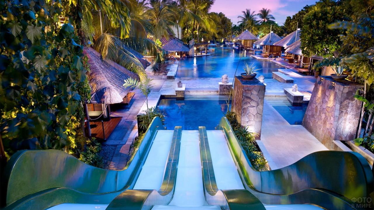 Пляж в отеле среди зелени с горкой и бунгало вокруг бассейна