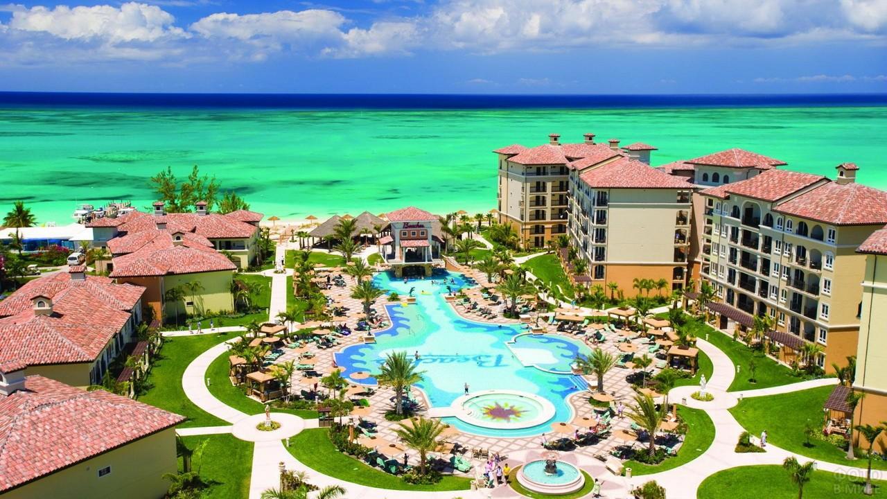 Пляж внутри территории отеля с зелёным газоном и выходом к морю