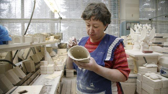 Сотрудница завода Гжель проверяет качество изделия