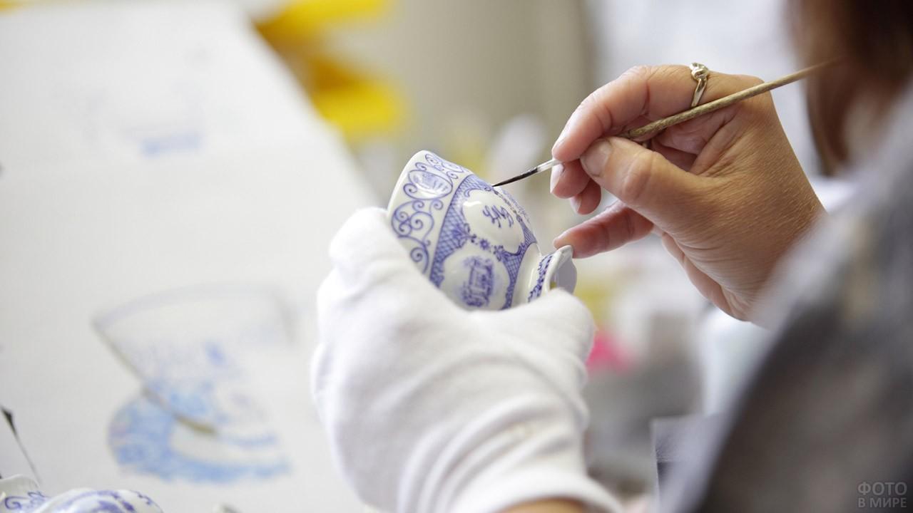 Женщина расписывает вручную чайную чашку
