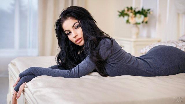 Черноволосая девушка лежит на кровати