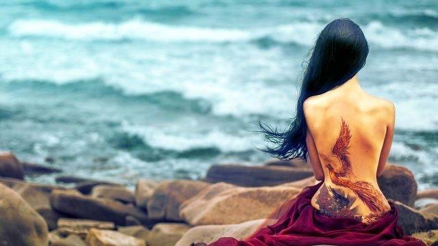Черноволосая девушка с татуировкой на спине