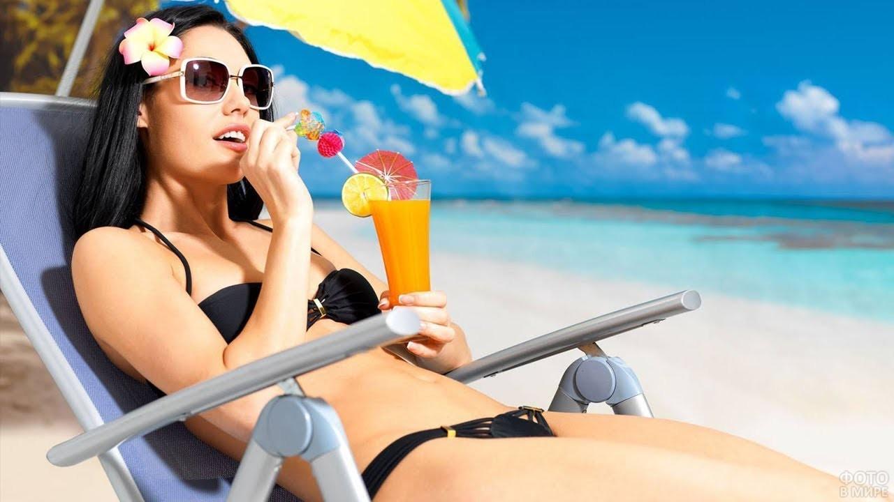 Девушка с коктейлем на пляже